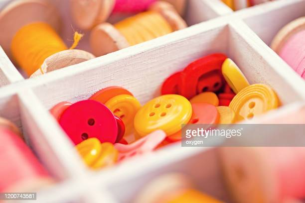 close-up box with sewing buttons set collection of yellow, red, pink white wooden box - button sewing item stock pictures, royalty-free photos & images