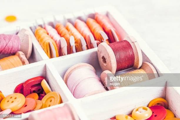 close-up box with sewing set collection of yellow, red, pink spools threads arranged in a white wooden box - button sewing item stock pictures, royalty-free photos & images