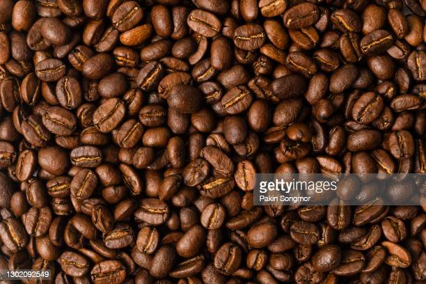 close-up brown coffee beans background. - focus on background stock pictures, royalty-free photos & images