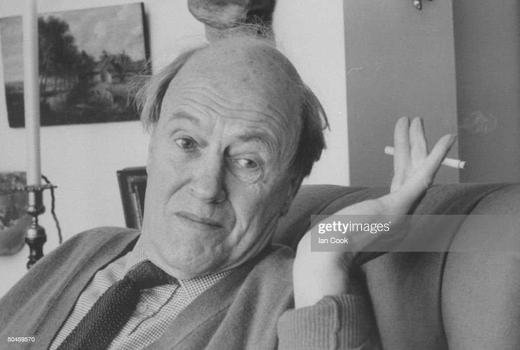 Closeup candid portrait of writer Roald Dahl waving a cigarette while talking at home.