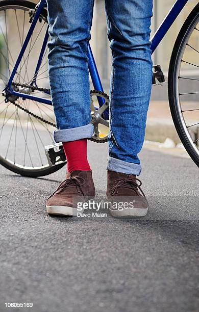 close-up  commuter cyclists feet with one red sock - rolled up trousers stock pictures, royalty-free photos & images