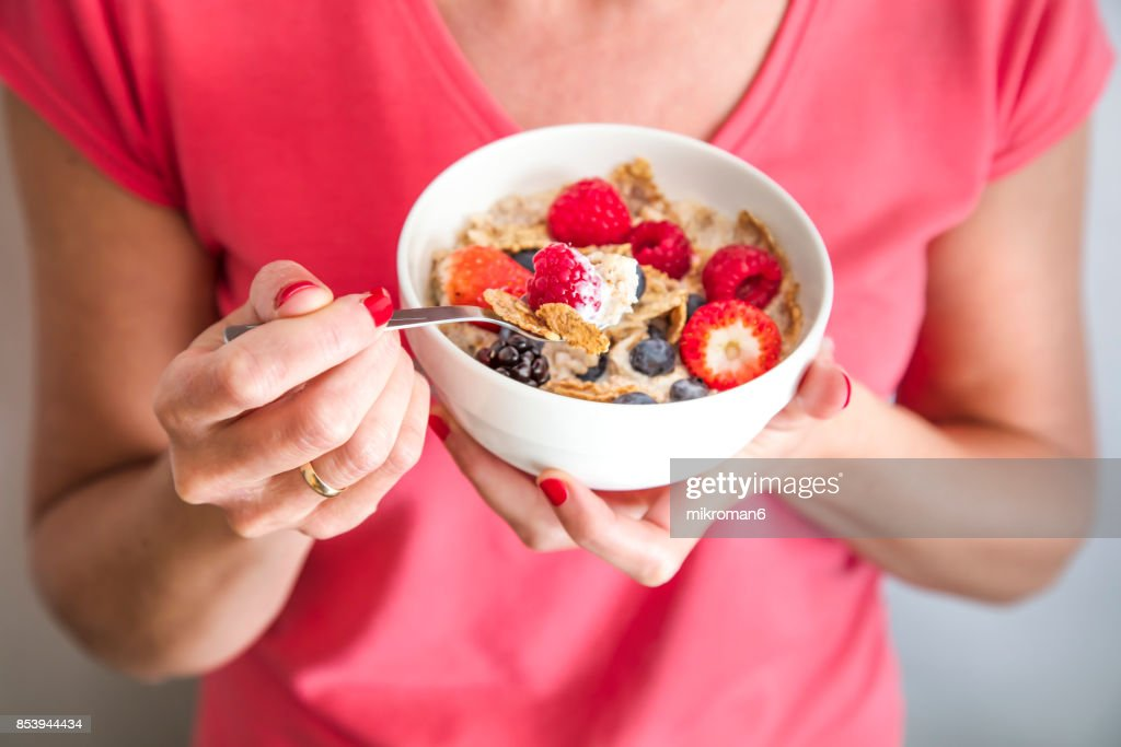 Close-up crop of woman holding a bowl containing Homemade granola or muesli with oat flakes, corn flakes, dried fruits with fresh berries. Healthy Breakfast
