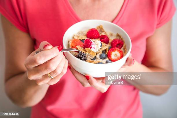 close-up crop of woman holding a bowl containing homemade granola or muesli with oat flakes, corn flakes, dried fruits with fresh berries. healthy breakfast - unhealthy living stock pictures, royalty-free photos & images