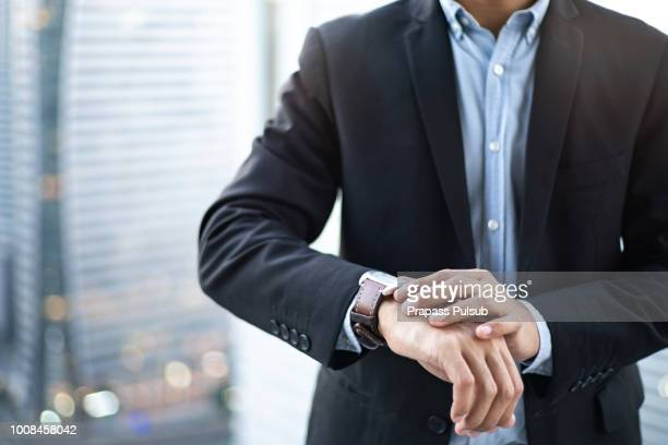 closeup designer watch on businessman hand, he looks on the time and hurrying - ver a hora imagens e fotografias de stock