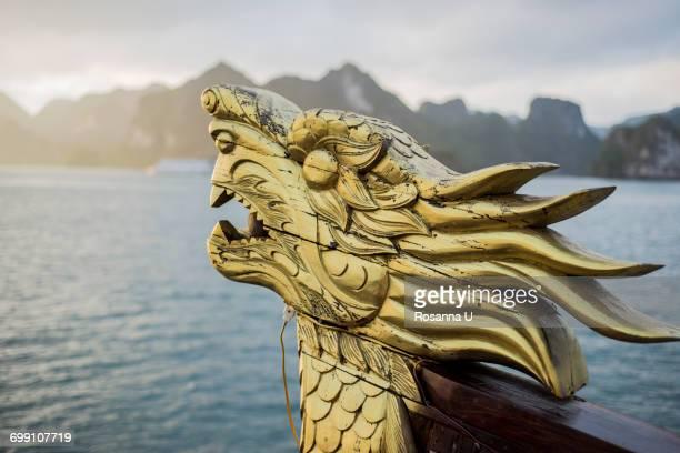 """close-up detail of dragon head on boat at sunrise, ha long bay, vietnam"" - human face foto e immagini stock"