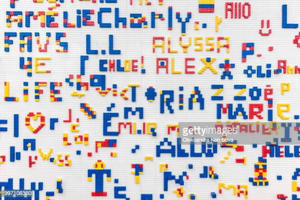 close-up details of a home-made wall full of names made from colorful puzzle blocks. - the_writer's_block stock pictures, royalty-free photos & images