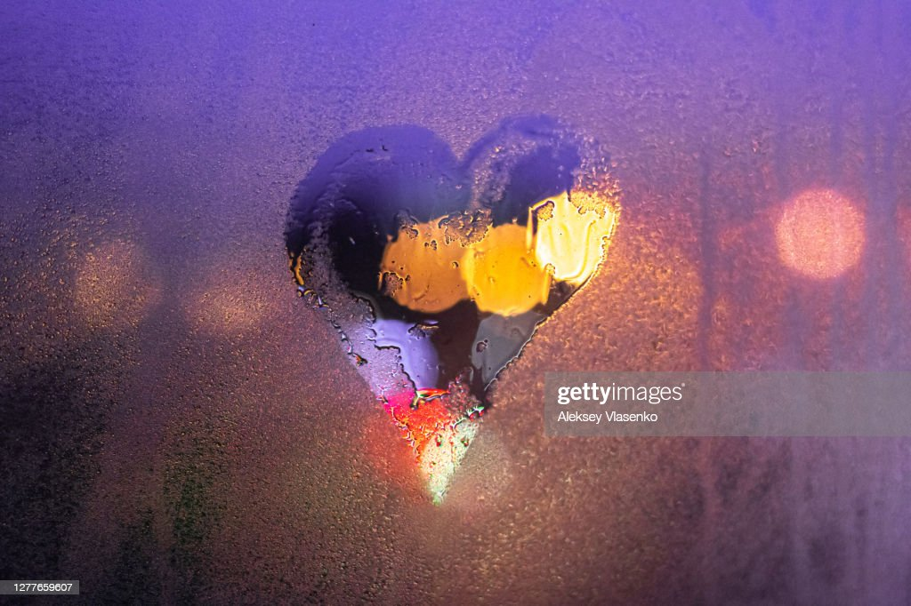 Close-up drawn heart on a foggy wet window : Stock Photo