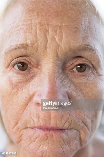 Closeup face of mature woman, front view, no makeup