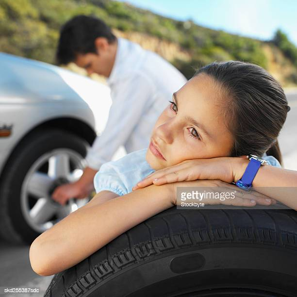 Close-up father changing flat tire of car and daughter holding spare wheel (8-9)