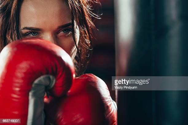 Close-up female boxer wearing punching gloves at gym
