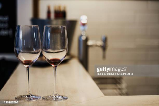 close-up front view of two empty crystal wine glasses on a bar table with a metallic bucket with some opened wine bottles with cork and a beer faucet without jar at the back. horizontal photography. - cleaning after party stock pictures, royalty-free photos & images