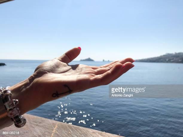 close-up girl hand in a sea background - acireale stock-fotos und bilder