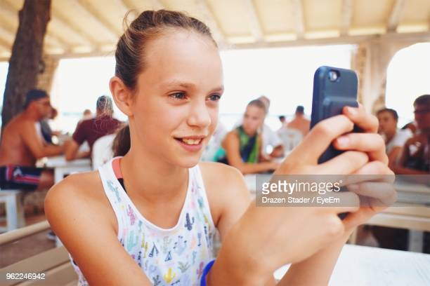 Close-Up Girl Using Mobile Phone At Table