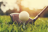 closeup golf club and golf ball on green grass wiht sunset