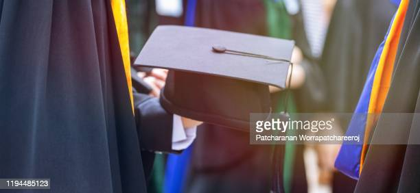 closeup graduation student hold hat in hand during commencement of graduates during commencement. congratulation in university concept, education concept. - master's degree stock pictures, royalty-free photos & images