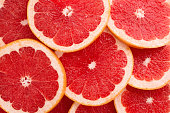 Close-up Grapefruit slices abstract background in Living Coral color.