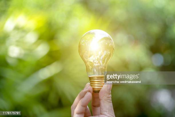 closeup hand holding light bulb while using on laptop, new ideas and creativity concept. - resourceful stock pictures, royalty-free photos & images