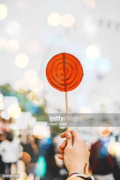 closeup hand holding lollipop - lollipop stock pictures, royalty-free photos & images
