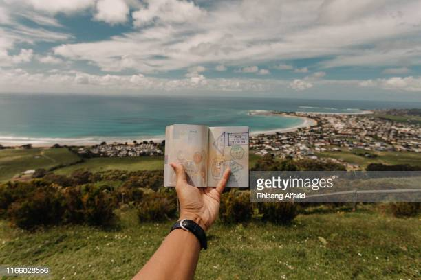 close-up hand holding passport against beach - thisisaustralia stock pictures, royalty-free photos & images