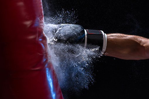 Close-up hand of boxer at the moment of impact on punching bag over black background 997048118