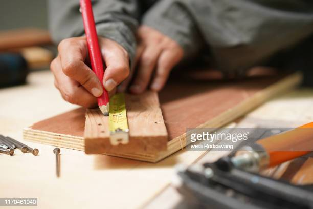 closeup hand of carpenter using tape measure to measure distance and marking with pencil - installing stock pictures, royalty-free photos & images
