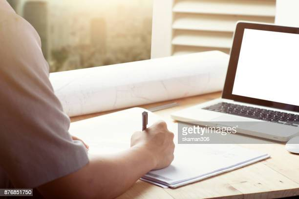 Close-up hand Of male Architect Drawing Blueprint on work space wooden table in office