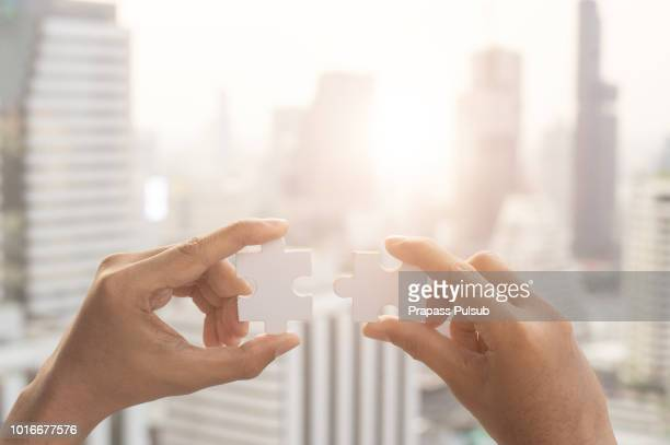 closeup hand of woman connecting jigsaw puzzle with sunlight effect, business solutions, success and strategy concept - oplossing stockfoto's en -beelden