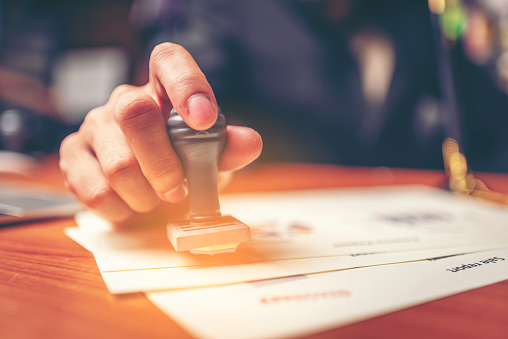 Close-up hand stamping of businessman for signing approval on documents , business concept 1013627700