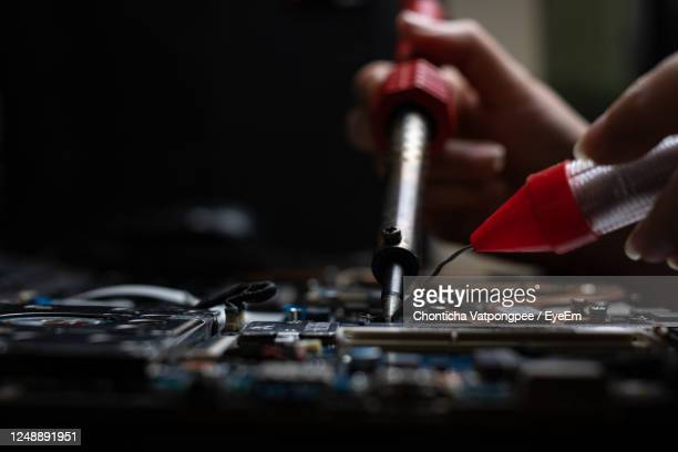 close-up hand technician repairing broken laptop notebook computer with electric soldering iron - desktop pc stock pictures, royalty-free photos & images