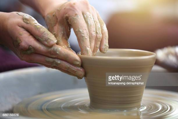 closeup hands of a potter, creating an earthen jar on the traditional machine