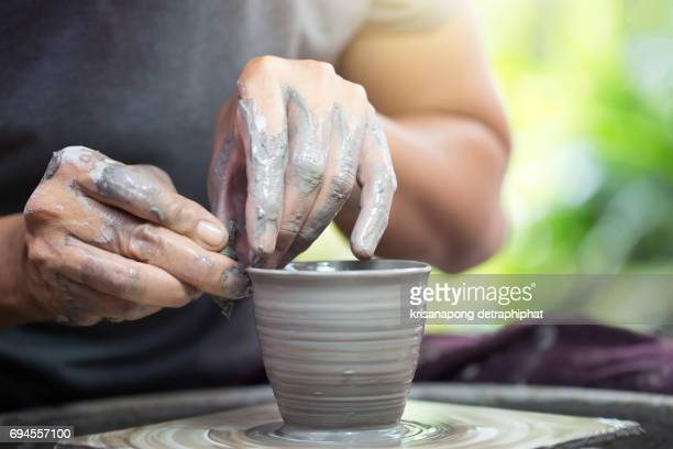 closeup hands of a potter, creating an earthen jar on the traditional machine - potter stock pictures, royalty-free photos & images