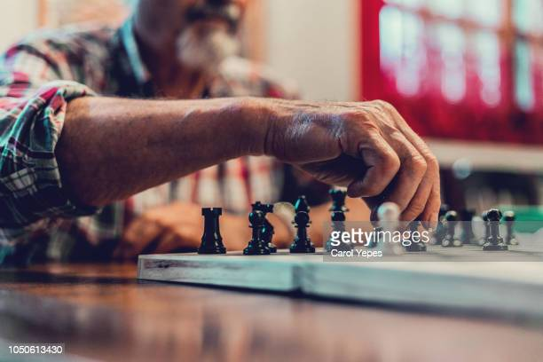 closeup hands senior man playing  chess - human body part stock-fotos und bilder