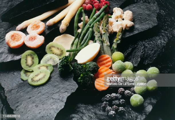 close-up high angle view of frozen food on rock - frozen fruit stock pictures, royalty-free photos & images