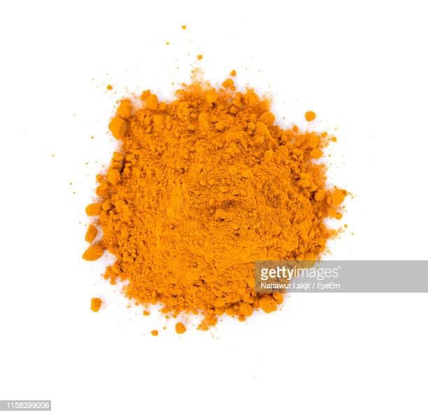 close-up high angle view of ground turmeric over white background - gemahlen stock-fotos und bilder