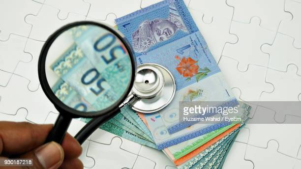 Close-Up High Angle View Of Hand Holding Magnifying Glass Over Stethoscope And Money On Puzzle
