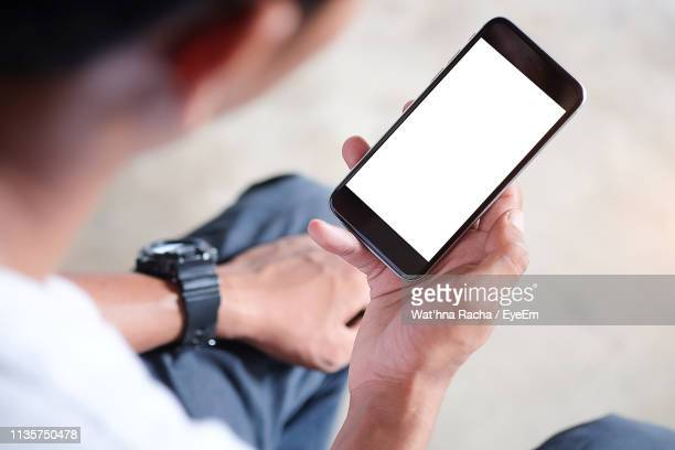 close-up high angle view of man using smart phone - over the shoulder view stock pictures, royalty-free photos & images