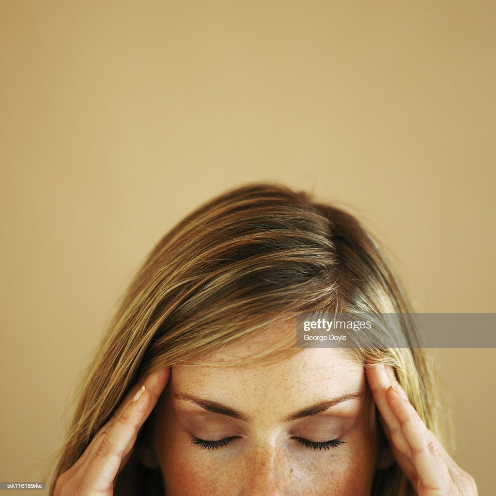 Close-up high section of a young woman touching her head with eyes closed : Stock Photo