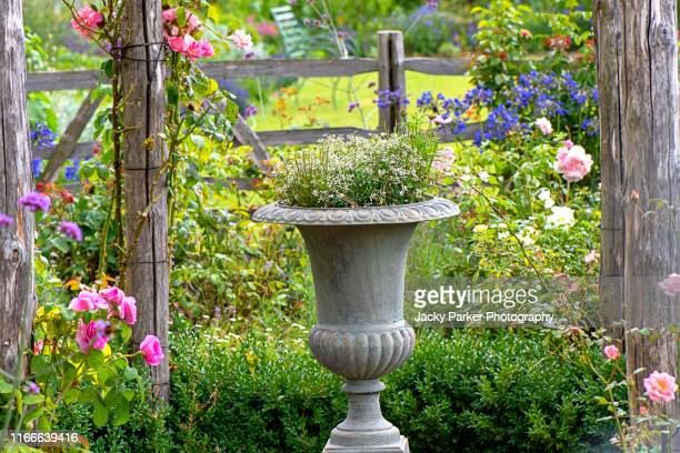 close-up image of a concrete rustic garden planter in an english cottage garden with soft pink roses - grounds stock pictures, royalty-free photos & images