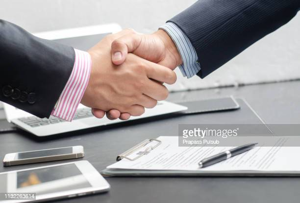 close-up image of a firm handshake between two colleagues after signing a contract - promotion employment stock pictures, royalty-free photos & images