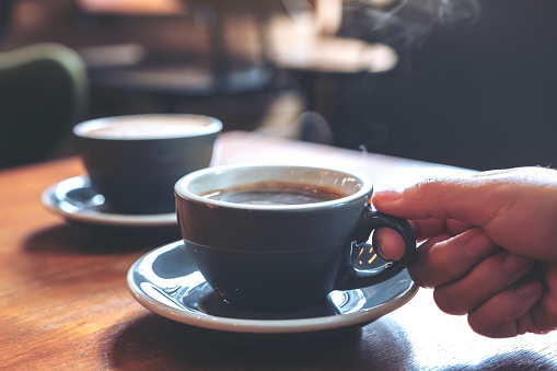 Closeup image of a hand holding a blue cup of hot coffee with smoke on wooden table in cafe 1030155158
