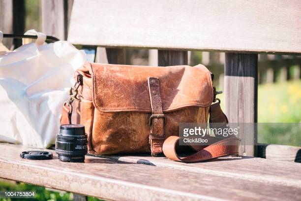 Close-up image of a leather camera bag on a park bench in a sunny day (outdoors)