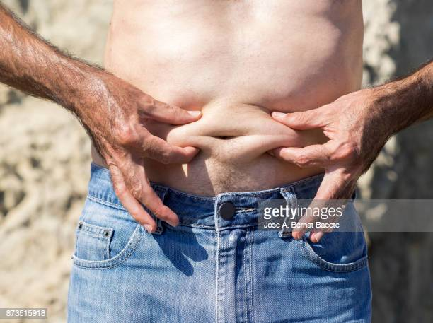 a close-up image of a men mature with  belly fat pinching itself, white-skinned, with jeans shorts in the light of the sun in the beach - barriga de cerveja imagens e fotografias de stock