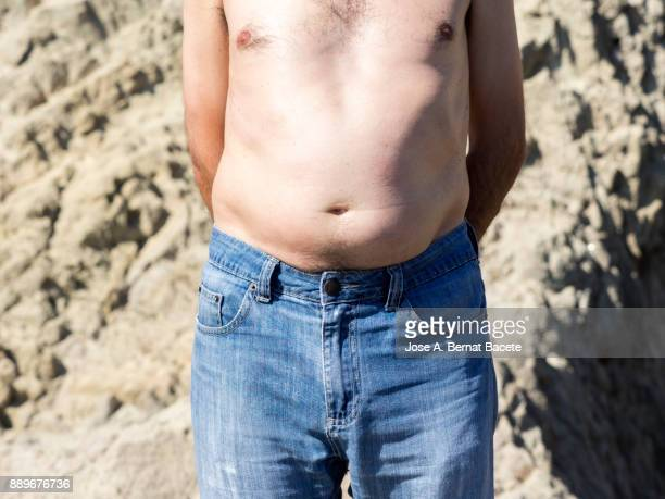 A close-up image of a men mature with  belly fat pinching itself, white-skinned, with jeans shorts in the light of the Sun in the beach