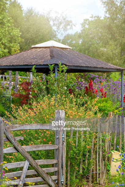 close-up image of a rustic wooden gate leading to a colourful garden and wooden pergola/gazebo - gazebo stock pictures, royalty-free photos & images