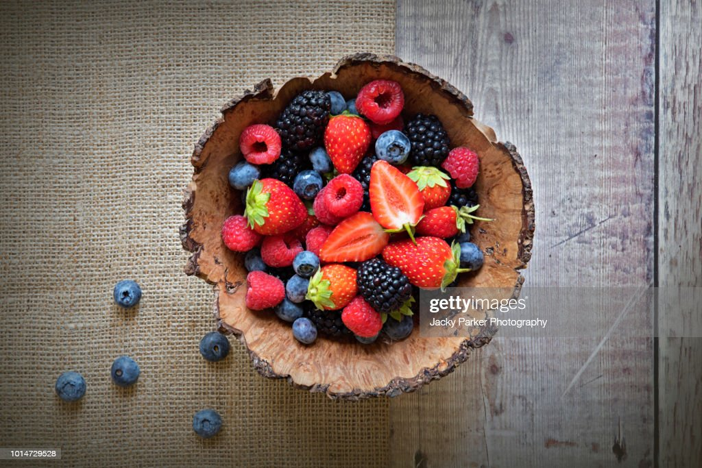 Close-up image of a wooden bowl full of Healthy Summer berries including Strawberries, raspberries, black berries and blue berries. : Stock Photo