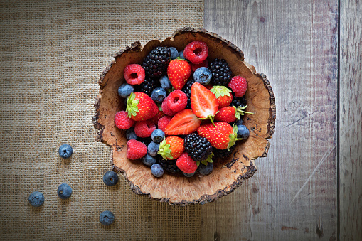 Close-up image of a wooden bowl full of Healthy Summer berries including Strawberries, raspberries, black berries and blue berries. - gettyimageskorea
