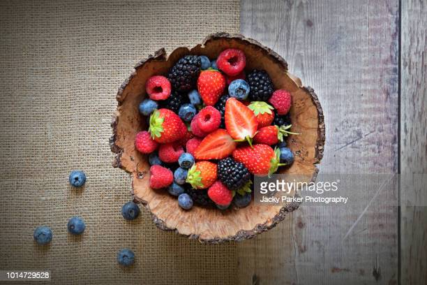 close-up image of a wooden bowl full of healthy summer berries including strawberries, raspberries, black berries and blue berries. - berry fruit stock pictures, royalty-free photos & images