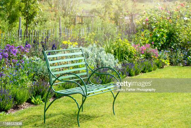 close-up image of a wrought iron, green garden seat by a summer herbaceous border - 庭園 ストックフォトと画像