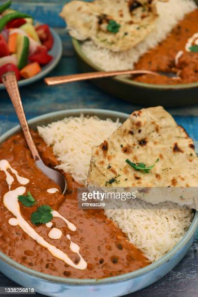 close-up image of blue bowls containing homemade dal makhani (black lentils and red kidney bean curry) meals, served with white rice and naan flatbread, metal spoons, side salad, blue wood grain background, focus on foreground - side salad stock pictures, royalty-free photos & images
