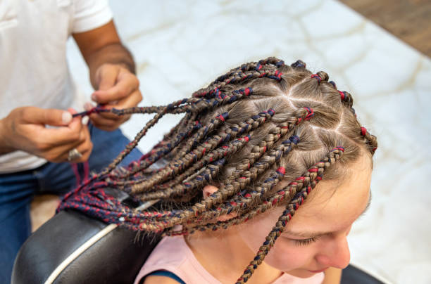 Closeup image of hands making braids on a girl's head.